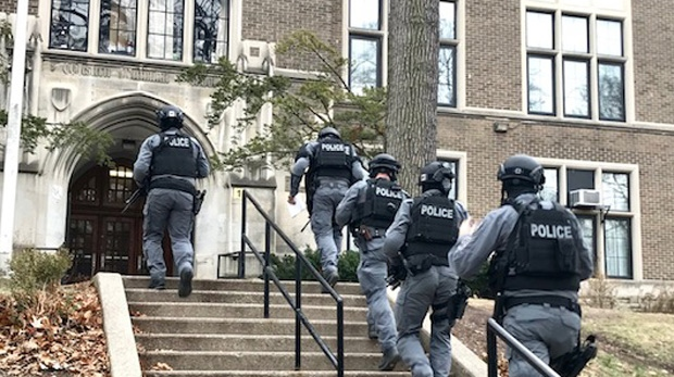Toronto police tactical unit members enter Western Technical Commercial School on Dec. 6 after receiving reports about a person with a gun inside. (Cristina Tenaglia/CP24)