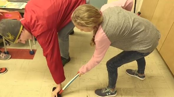 Students get a sweeping tutorial form Harman, a  Special Olympics curling athlete