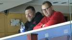 Former Calgary Flame Brian McGrattan watches the team practice on December 6 alongside GM Brad Treliving