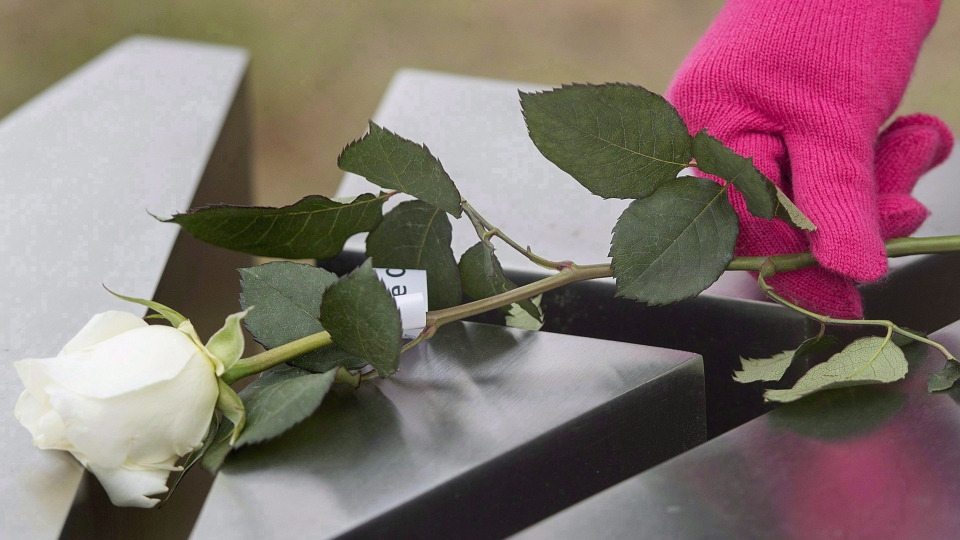 A woman places a rose on a memorial of one of the 14 women murdered at Ecole Polytechnique on December 6, 1989, during a ceremony to mark the 26th anniversary of the massacre, in Montreal, on Sunday, Dec. 6, 2015. THE CANADIAN PRESS/Graham Hughes