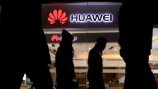 Pedestrians walk past a Huawei retail shop in Beijing Thursday, Dec. 6, 2018. (AP Photo/Ng Han Guan)