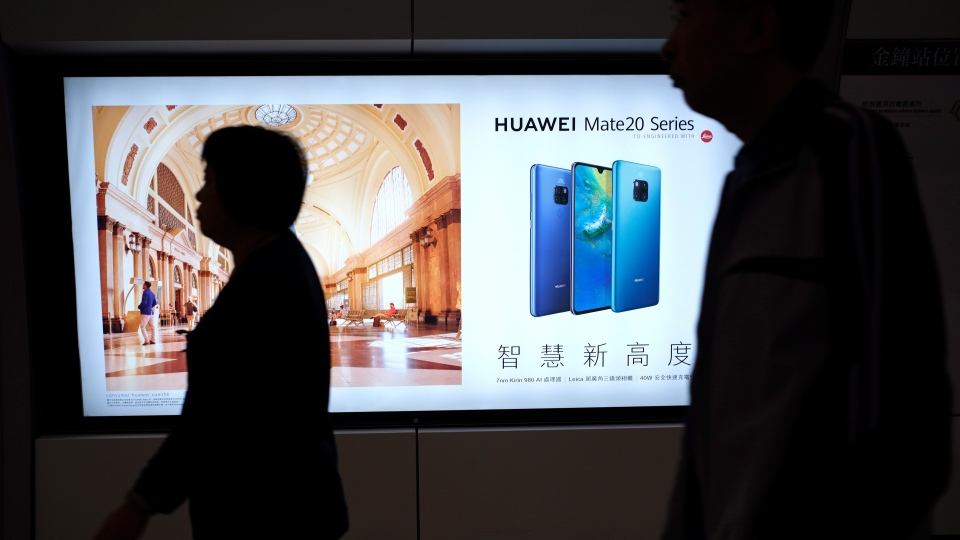 People walk past an advertisement for Huawei at a subway station in Hong Kong Thursday, Dec. 5, 2018. (AP Photo/Vincent Yu)