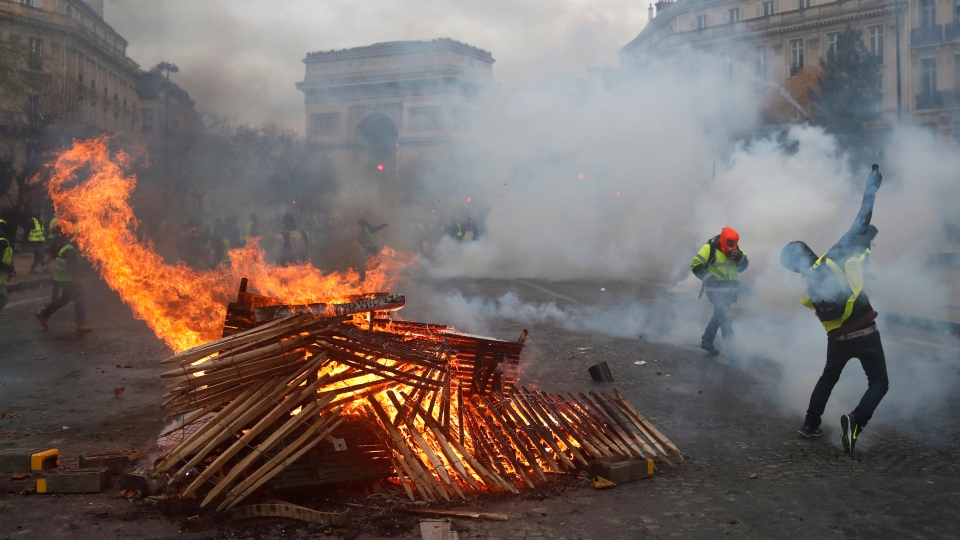 In this Dec. 1, 2018 file photo, demonstrators throw items near a burning barricade near the Arc de Triomphe during a demonstration. (AP Photo/Thibault Camus, File)