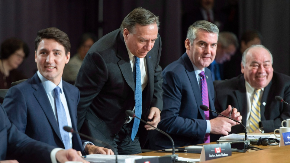 Quebec Premier Francois Legault takes his seat in between Prime Minister Justin Trudeau, and Premiers Stephen McNeil of Nova Scotia and Bob McLeod of the Northwest Territories during the first ministers meeting in Montreal on Friday, December 7, 2018. THE CANADIAN PRESS/Paul Chiasson