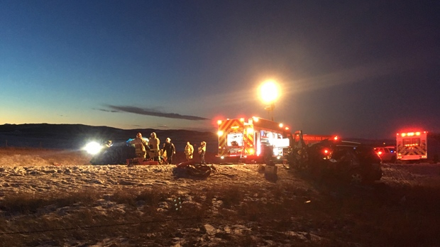 Emergency crews in a field of debris following Friday afternoon's head-on crash on Highway 7 east of Black Diamond