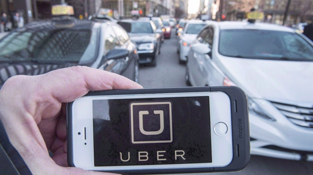The Uber logo is seen in front of protesting taxi drivers at the courthouse in Montreal, Tuesday, Feb. 2, 2016. THE CANADIAN PRESS/Ryan Remiorz