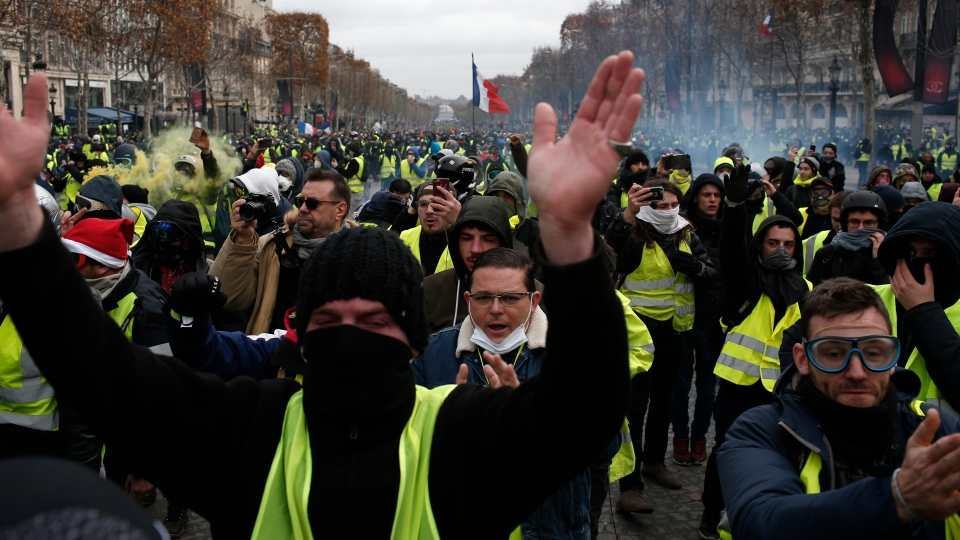 Demonstrators wearing yellow vests gather on the Champs-Elysees avenue Saturday, Dec. 8, 2018 in Paris. (AP Photo/Rafael Yaghobzadeh)