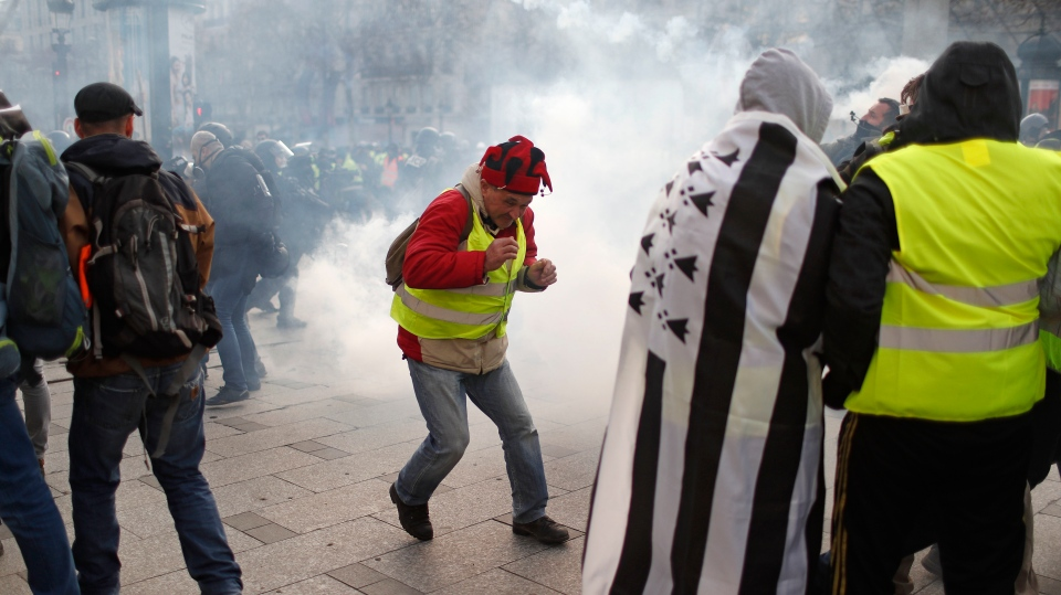 A teargas canister falls among demonstrators wearing yellow vests Saturday, Dec. 8, 2018 in Paris.  (AP Photo/Thibault Camus)