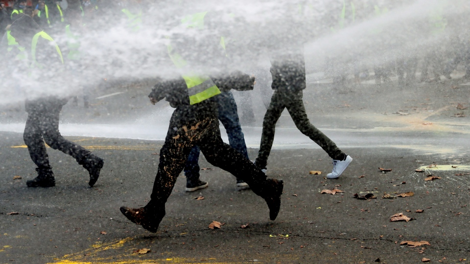 Protesters run after being sprayed by a police water cannon during a demonstration in Brussels, Saturday, Dec. 8, 2018.  (AP Photo/Francisco Seco)