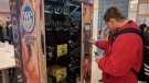 This Dec. 7, 2018 photo shows Ohio State University sophomore Nick Vales buys a package of bacon slices from a vending machine available on the Columbus campus. [JD Malone/The Columbus Dispatch via AP)