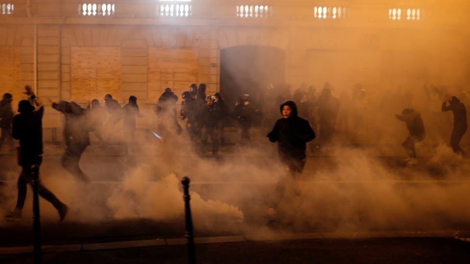 Demonstrators run away to avoid tear gas during clashes Saturday, Dec. 8, 2018 in Paris. (AP Photo/Rafael Yaghobzadeh)