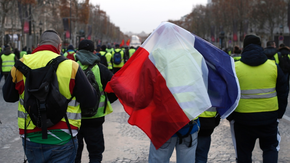 Demonstrators wearing yellow vests, one covered with the French flag, march down the Champs Elysees avenue Saturday, Dec. 8, 2018 in Paris. (AP Photo/Rafael Yaghobzadeh)