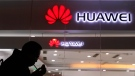 A man lights a cigarette outside a Huawei retail shop in Beijing Thursday, Dec. 6, 2018. China on Thursday demanded Canada release a Huawei Technologies executive who was arrested in a case that adds to technology tensions with Washington and threatens to complicate trade talks. (AP Photo/Ng Han Guan)