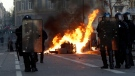 Riot police officer stand in front a burning trash bin during clashes, Saturday, Dec. 8, 2018 in Marseille, southern France. (AP Photo/Claude Paris)