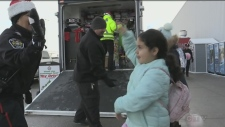 A member of the South Simcoe Police high-fives a child after donating to the Command Post Toy Drive in Bradford on Saturday, December 8, 2018 (KC Colby/CTV News)