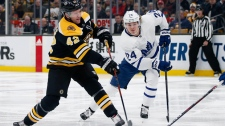 Boston Bruins' David Backes (42) takes a shot as Toronto Maple Leafs' Kasperi Kapanen (24) defends during the second period of an NHL hockey game in Boston, Saturday, Dec. 8, 2018. (AP Photo/Michael Dwyer)
