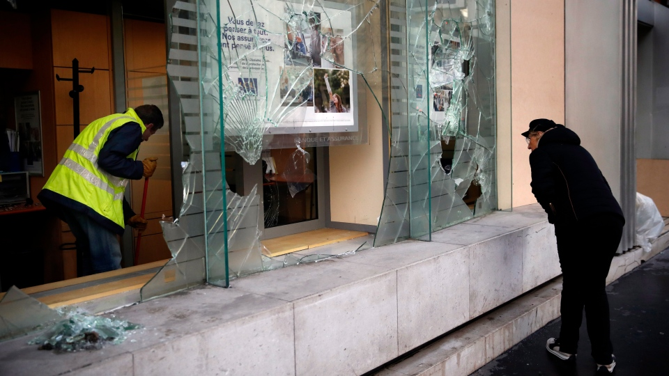 A worker clears debris in a bank as a man watches through smashed windows, in Paris, Sunday, Dec. 9, 2018. (AP Photo/Christophe Ena)