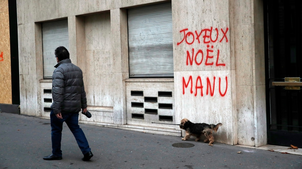 A man walks his dog past a tag reading : Happy Christmas Manu, referring to French President Emmanuel Macron, in Paris, Sunday, Dec. 9, 2018. (AP Photo/Christophe Ena)