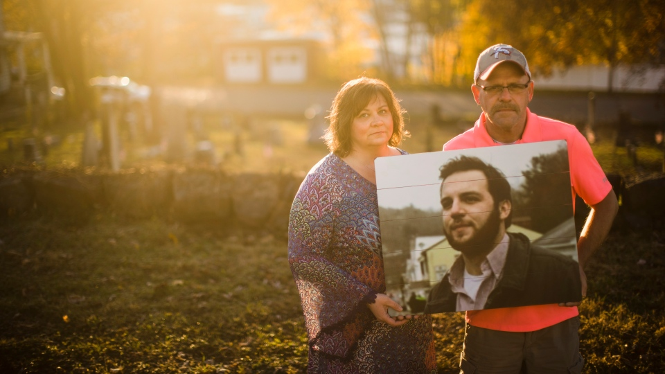 In this Nov. 8, 2018 photo, Janel Wentz and Tim Firestone pose for a photograph in Port Carbon, Pa. while holding an image of their late son former Mount Carbon Mayor Brandon Wentz. (AP Photo/Matt Rourke)