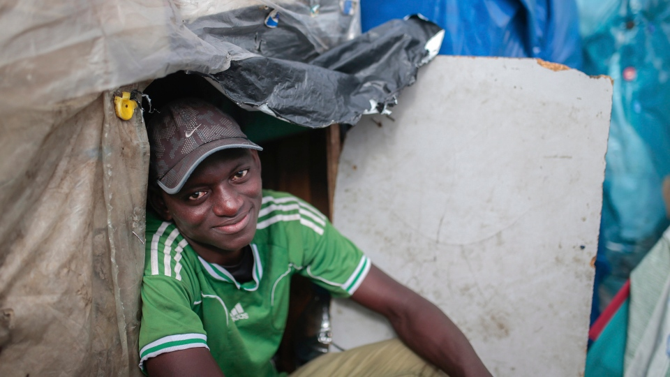 Wazzizi, a sub-Saharan migrant from Guinea, sits outside the tent where he lives at at Ouled Ziane camp in Casablanca, Morocco, Thursday, Dec. 6, 2018. (AP Photo/Mosa'ab Elshamy)