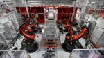 In this May 14, 2015 photo, Kuka robots work on Tesla Model S cars in the Tesla factory in Fremont, Calif. (AP Photo/Jeff Chiu)