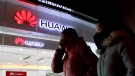 Women walk past a Huawei retail shop in Beijing Thursday, Dec. 6, 2018. (AP / Ng Han Guan)