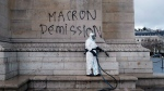 A worker is about to clean a graffiti reading 'Macron resignation' on the Arc de Triomphe the day after a demonstration, in Paris, Sunday, Dec. 2, 2018. (AP / Thibault Camus)