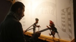 Syrian shadow puppeteer Shadi al-Hallaq is seen moving his puppets Karakoz (R) and Eiwaz (L) from inside his booth during a presentation in Damascus. (LOUAI BESHARA / AFP)