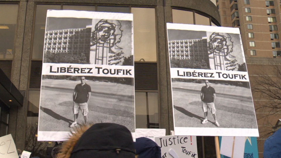 One of the signs held by protesters gathered in Montreal to support a father who's been stuck in Cuba for over a year and now faces a second trial for his involvement in a fatal boating accident.