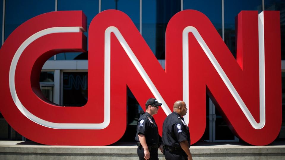 Security guards walk past the entrance to CNN headquarters, Tuesday, Aug. 26, 2014, in Atlanta. (AP Photo/David Goldman)