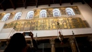In this Thursday, Dec. 6, 2018 photo, a visitor photographs a renovated part of a fresco inside the Church of the Nativity, built atop the site where Christians believe Jesus Christ was born, in the West Bank City of Bethlehem. (AP Photo/Majdi Mohammed)