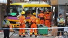 Workers inspect the school bus which plowed onto a sidewalk in Hong Kong Monday, Dec. 10, 2018. The parked 19-seat school bus slipped downhill toward a busy intersection, police said. (Apple Daily via AP)