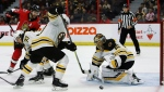 Boston Bruins goaltender Tuukka Rask (40) looks to scoop up a loose puck in front of the net during second period NHL hockey action against the Ottawa Senators, in Ottawa on Sunday, Dec. 9, 2018. THE CANADIAN PRESS/Fred Chartrand
