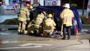 Firefighters rescue a man trapped inside a flipped car in Burnaby, B.C. on Dec. 9, 2018.