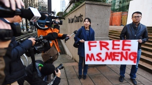 People hold a sign at a B.C. courthouse prior to the bail hearing for Meng Wanzhou, Huawei's chief financial officer on Monday, December 10, 2018. (THE CANADIAN PRESS / Jonathan Hayward)