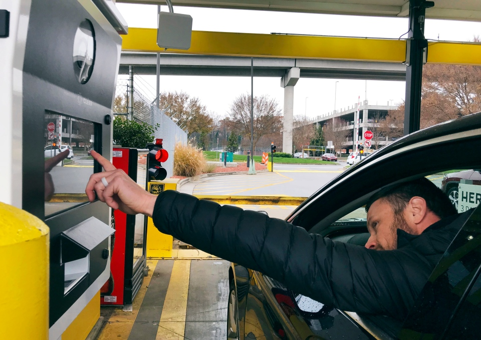 In this Friday, Dec. 7, 2018, photo, a rental car driver demonstrates a new biometric scanning machine by placing his finger on the reader at the Hertz facility at Hartsfield-Jackson Atlanta International Airport, in Atlanta. (AP Photo/Jeff Martin)