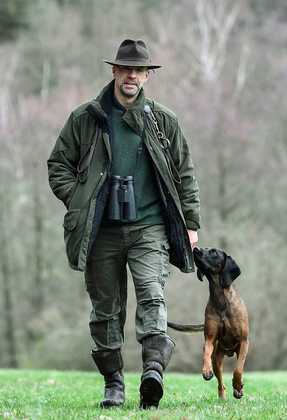In this Dec. 7, 2018 photo Dirk Gratzel walks with his dog at his hunting ground in Stollberg, western Germany. (AP Photo/Martin Meissner)