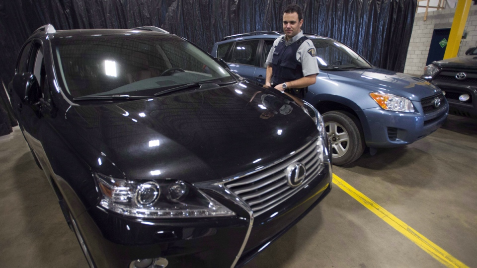 RCMP Investigator Maxime Deschenes looks at a stolen Lexus that was seized from a container in Montreal. (Ryan Remiorz / THE CANADIAN PRESS)