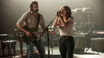 This image released by Warner Bros. shows Bradley Cooper, left, and Lady Gaga in a scene from the latest reboot of the film, 'A Star is Born.' (Neal Preston/Warner Bros. via AP)