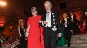 Physics 2018 Nobel laureate Donna Strickland and King Carl Gustaf of Sweden arrive for the Nobel Prize banquet in Stockholm City Hall, Sweden, Monday Dec. 10, 2018. (Fredrik Sandberg/TT via AP)