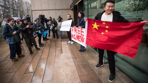 Supporters hold signs and a Chinese flag outside B.C. Supreme Court during the third day of a bail hearing for Meng Wanzhou, the chief financial officer of Huawei Technologies, in Vancouver, on Tuesday December 11, 2018. (THE CANADIAN PRESS/Darryl Dyck)