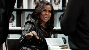 "In this Nov. 30, 2018, file photo, Former First Lady Michelle Obama signs books during an appearance for her book, ""Becoming,"" in New York. (AP Photo/Richard Drew, File)"