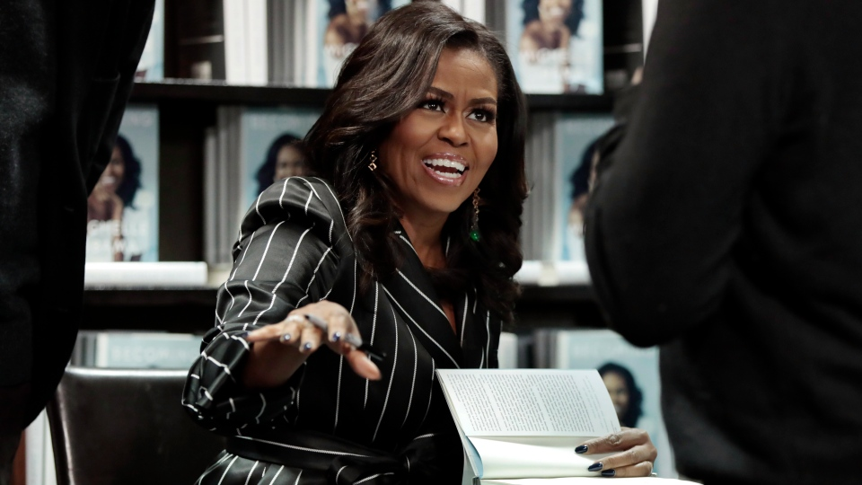 In this Nov. 30, 2018, file photo, Former First Lady Michelle Obama signs books during an appearance for her book,