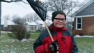 """In this Thursday, Nov. 29, 2018 photo, Kaleb Klakulak takes a break from raking leaves outside the home a home in Rochester Hills, Mich., as he raises money for a headstone for his best friend Kenneth """"K.J."""" Gross, who died of cancer last year. (Max Ortiz/Detroit News via AP)"""