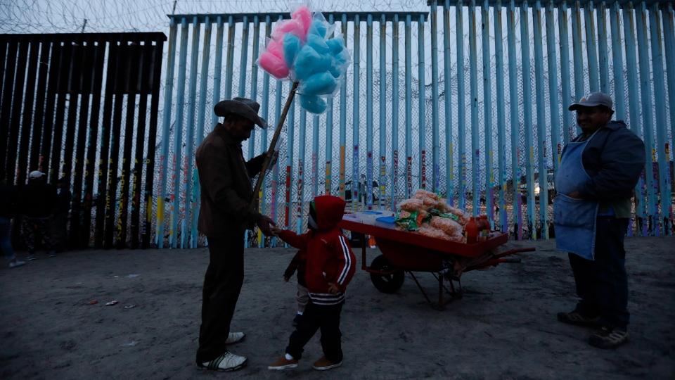 A Honduran migrant boy tries to buy cotton candy from a vendor, but doesn't have enough money, as migrants visit the U.S. border wall to look for opportunities to cross, on the beach in Tijuana, Mexico, Sunday, Dec. 9, 2018. (AP Photo/Rebecca Blackwell)