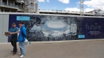 In this May 14, 2017, file photo, football fans smile as they pass a poster showing the plans for the new stadium, in front on construction work at White Hart Lane stadium in London. (AP Photo/Frank Augstein, File)