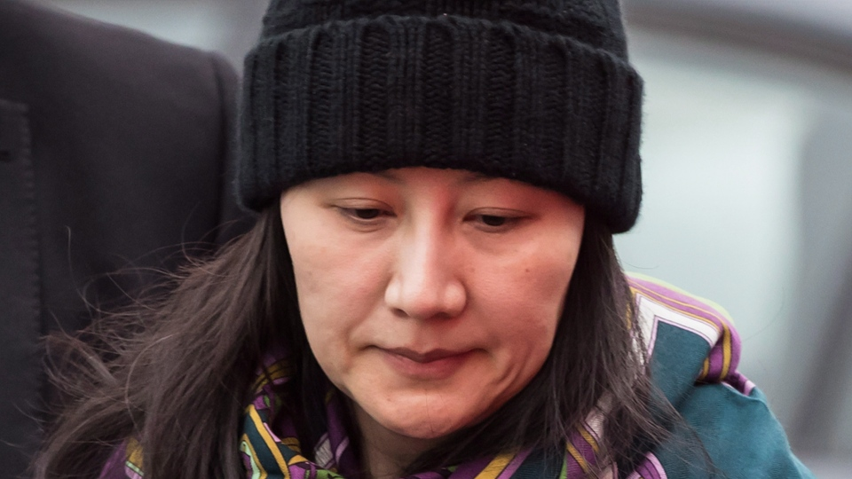 Huawei chief financial officer Meng Wanzhou is escorted by her private security detail while arriving at a parole office, in Vancouver, on Wednesday December 12, 2018. (THE CANADIAN PRESS/Darryl Dyck)