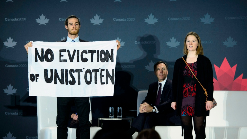 Protestors interrupt Minister of Finance Bill Morneau while he takes part in a Canada 2020 panel discussion moderated by The Canadian Presses Heather Scoffield in Ottawa on Thursday, Dec. 13, 2018. THE CANADIAN PRESS/Sean Kilpatrick