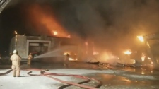 In this image from video crews battle a barn fire in Norfolk County, Ont. on Wednesday, Dec. 12, 2018. (@OPP_WR / Twitter)