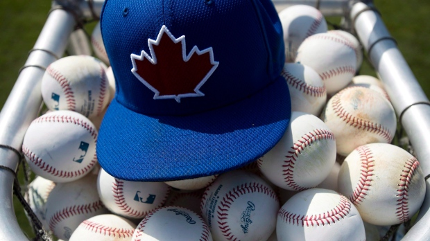 A Toronto Blue Jays practice hat sits on baseballs during baseball spring training in Dunedin, Fla., on February 21, 2013. The Toronto Blue Jays picked up right-handed pitcher Elvis Luciano from the Kansas City Royals on Thursday in the Rule 5 draft while losing Canadian right-hander Jordan Romano in the selection process. THE CANADIAN PRESS/Nathan Denette